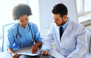 a doctor showing a document to another doctor